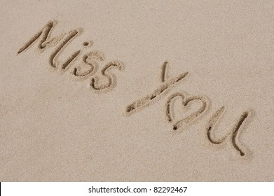 """The Words """"Miss You"""" Written in Sand on a Beach"""
