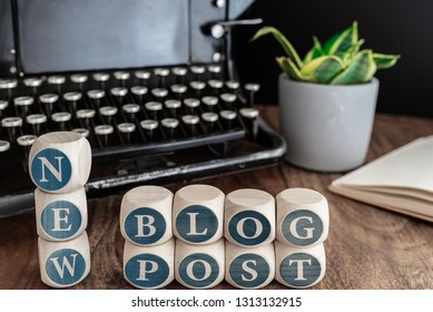 words NEW BLOG POST on wooden blocks against vintage typewriter, potted plant and note pad on table.