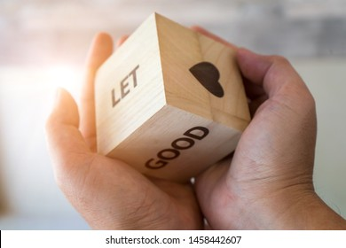 The words on wooden dice in the hands with lighting, there are six sides of cubes with heart,GOOD and LET to show.  Rules and laws in conducting selected your life.
