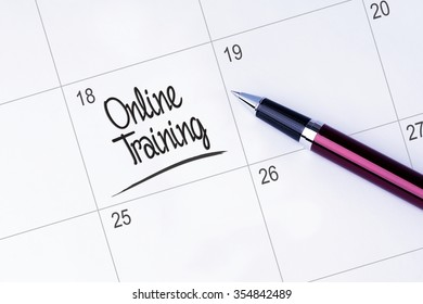The words Online Training on a calendar planner to remind you an important appointment with a pen on isolated white background.