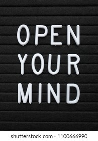 The words Open Your Mind in white plastic letters on a black letter board as an aid to learning and creativity