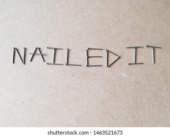 the words / phrase nailed it spelt out using silver steel nails / pins on a wooden block board background.