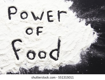 Words power of food written with flour on black background