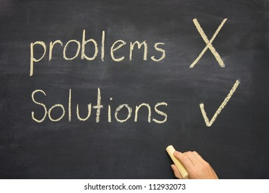 the words problems and solutions written on a blackboard / chalkboard with problems crossed and solutions ticked