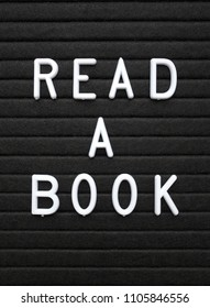 The words Read A Book in white plastic letters on a black letter board as a reminder