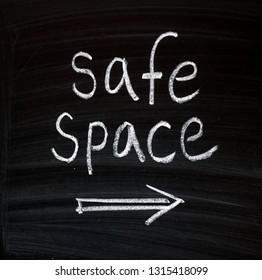 The words Safe Space written by hand in white chalk on a blackboard