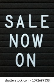 The words Sale Now On in white plastic letters on a black letter board as a reminder of an event promoting special offers