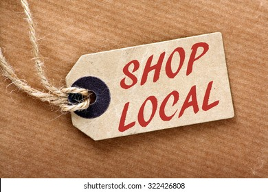 The words Shop Local in red text on a brown paper price label or luggage tag with string and wrapping paper