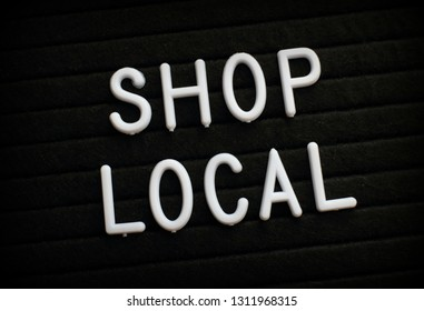 The words Shop Local in white plastic letters on a notice board