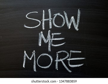 The words Show Me More written by hand in white chalk on a blackboard
