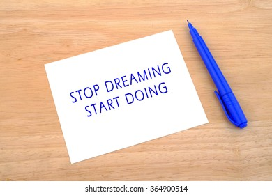 Words Stop Dreaming Start Doing written with pen on blank sheet paper over wooden background.
