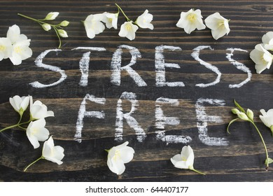 Words Stress Free with Jasmine Flowers on a Rustic Wooden Background.