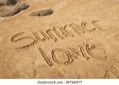 The words Summer Love written in the sand on the beach