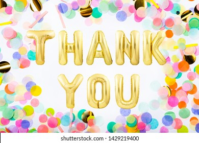 Words THANK YOU made of golden inflatable balloon letters in a frame made of colorful confetti on white background
