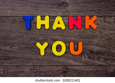 Words Thank you from wooden letters on dark wooden background