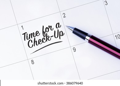 The words Time for a Check-Up written on a calendar planner to remind you an important appointment with a pen on isolated white background.