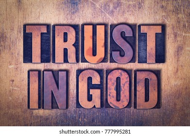 The words Trust in God concept and theme written in vintage wooden letterpress type on a grunge background.