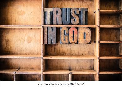 The words TRUST IN GOD written in vintage wooden letterpress type in a wooden type drawer.