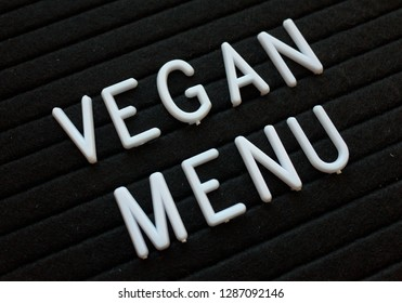 The words Vegan Menu in white plastic letters on a black letter board photographed at an angle