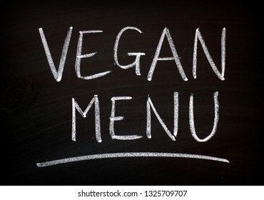 The words Vegan Menu written by hand in white chalk on a blackboard