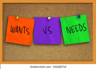 The words wants vs needs written on sticky colored paper over cork board