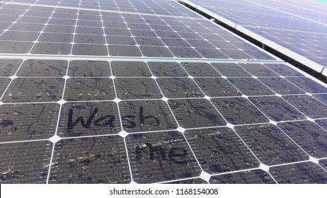 """The words """"wash me"""" written onto dusty, dirty solar panel"""