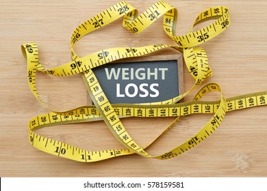 Words WEIGHT LOSS written on chalkboard with measuring tape on wooden background. Concept of weight loss, weight management,changing to healthier lifestyle,weight loss health issue and social issue