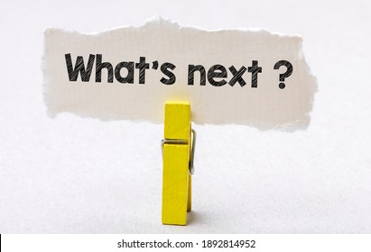 The words What's next written on a small piece of paper and a white background. Concept for business.