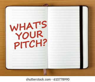 The words What's Your Pitch in red text on the page of an open notebook as a reminder to prepare your business idea or product for market