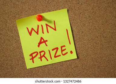 The words Win A Prize written by hand in red ink on a yellow sticky note pinned to a cork notice board as an incentive