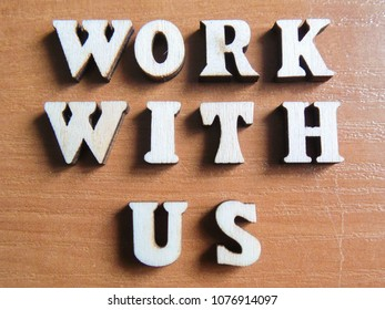 The words 'work with us' made of wooden letters. wood inscription on table