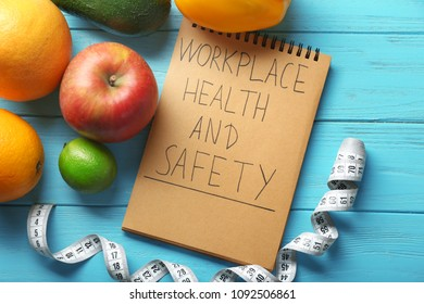 """Words """"Workplace, health and safety"""" written in notebook, fruits and measuring tape on wooden background"""