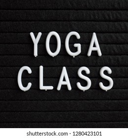 The words Yoga Class in white plastic letters on a black letter board as a reminder to take care of your physical health