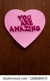 the words you are amazing in glitter letters on a pink heart stuck on a wooden cabinet