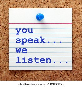 The words You Speak We Listen in blue text on a note card pinned to a cork notice board as a reminder of the way to provide excellent customer service via effective communication