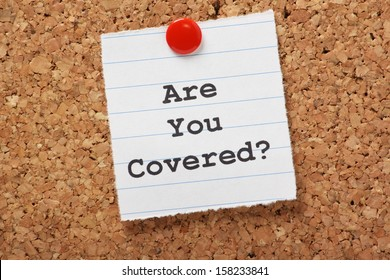 The words Are You Covered? typed on a scrap of lined paper and pinned to a cork notice board. Asking the question, are you insured for your car, travel, home or other liability.