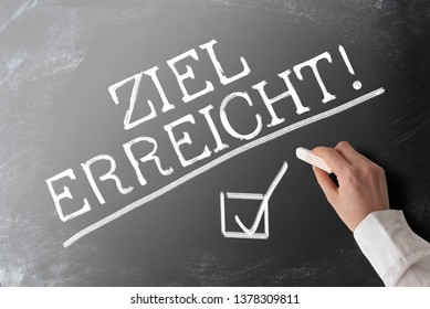 words ZIEL ERREICHT, German for goal accomplished,  with checkmark on blackboard