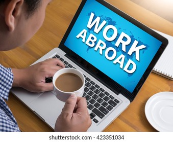 WORK ABROAD Businessman at work. Close-up top view of man working on laptop while sitting at the wooden desk , coffee