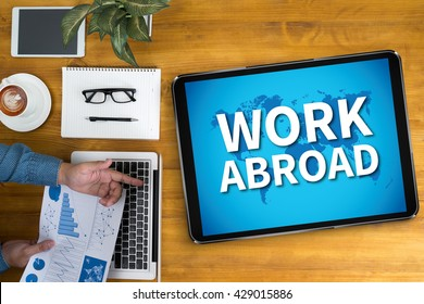WORK ABROAD Businessman working at office desk and using computer and objects, coffee, top view,
