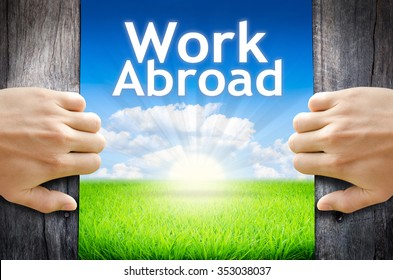 """Work Abroad. Hand opening an old wooden door and found wording """"Work Abroad"""" over green field and bright blue Sky Sunrise."""