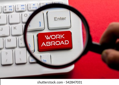 WORK ABROAD word written on keyboard view with magnifier glass