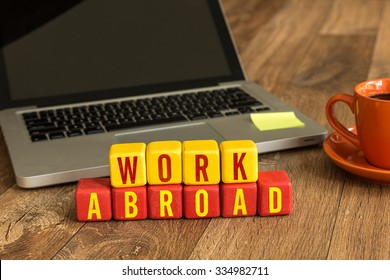 Work Abroad written on a wooden cube in front of a laptop