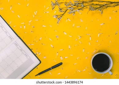 Work area Concept of coffee cups with notes book and pens with white flowers placed on the table on the floor Pastel yellow Top view Placed flat Summer, education, modern, read a book, book, Write