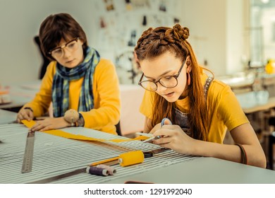 Work in atelier. Red-haired girl with nice hairstyle holding scissors working in atelier with her brother