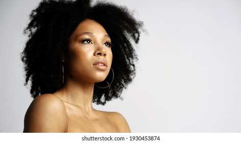 Work in the beauty field. Portrait of a young female model of Afro-appearance posing. Perfect, Healthy, Clean, facial skin. Black healthy curly hair.