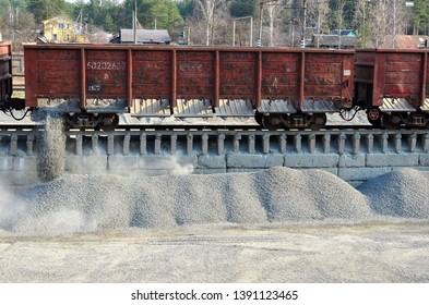 Work with bulk cargo. Unloading of crushed stone a railway car of a dump truck, closeup.  Unloading bulk cargo from railway wagons on high railway platform