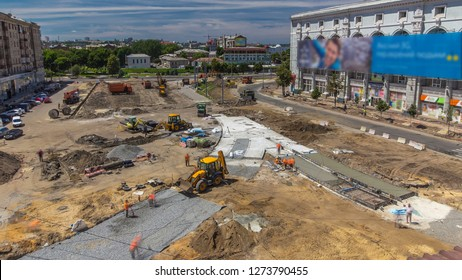 Work bulldozers and excavators on the construction of a road timelapse. Crushed stone on substrate. Support activities and road under construction. Reconstruction of tram tracks. Aerial top view from
