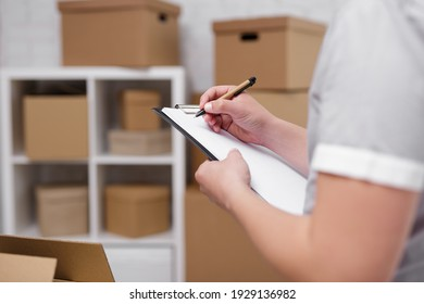 work and business concept - close up of male hands writing something in clipboard in warehouse