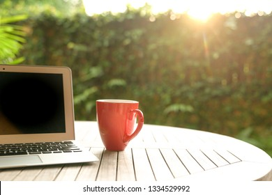 Work concept: Laptop and a red mug on a wooden table next to garden during sunset