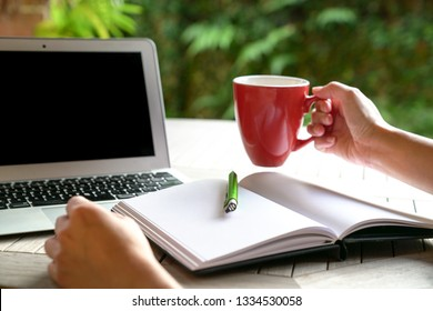 Work concept: One hand on red mug and another on table with laptop and note pad in view